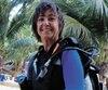 Martine Cuggia en Jamaïque, son équipement de plongée sous-marine sur le dos.