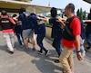 La police indonésienne escorte un groupe d'hommes lors d'un raid organisé en mai 2017, en raison de leur orientation sexuelle.