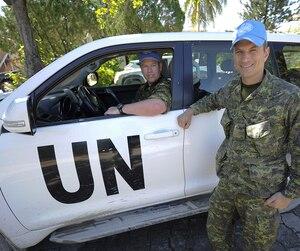 Le major François Dufault, au volant, et le major Alain Aube, à l'extérieur du véhicule, de la base militaire de Valcartier en patrouille dans les rues de Port-au-Prince.