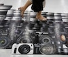 Man walks on an advertisement for Canon digital cameras at an electronics retail store in Tokyo