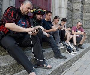 Des joueurs de Pokemon Go se sont réunis lundi sur le parvis de l'église St-Roch. L'application connaît un grand succès ici, même si elle n'est pas encore officiellement offerte au Canada.