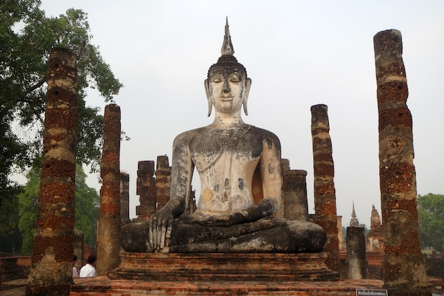 Un immense bouddha, vestige du 13e siècle,  dans le parc historique de Sukhothai.