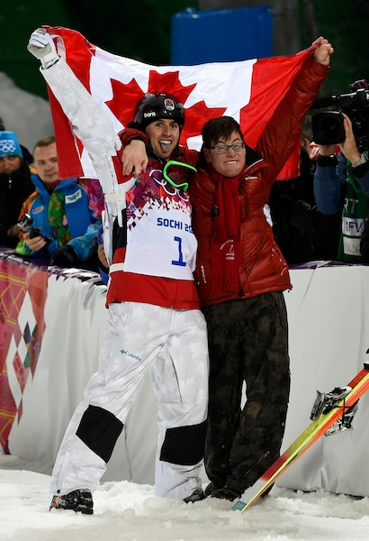 Winner Canada's Alex Bilodeau (L) and his brother Frederic celebrate after the men's freestyle skiing moguls finals at the 2014 Sochi Winter Olympic Games in Rosa Khutor, February 10, 2014.                     REUTERS/Dylan Martinez (RUSSIA  - Tags: SPORT OLYMPICS SPORT SKIING)