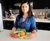 Suzanne Lepage, nutritionniste à l'organisme Dispensaire diététique de Montréal, est photographiée derrière des fruits et des légumes qu'elle conseille de se procurer dans son panier à provisions nutritif, afin de combler tous les besoins.