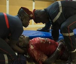 Des premiers répondants français viennent en aide à un homme portant un chandail d'Équipe Canada, à la suite de l'attaque terroriste à l'hôtel Splendid de Ouagadougou et au café Cappucino, samedi.