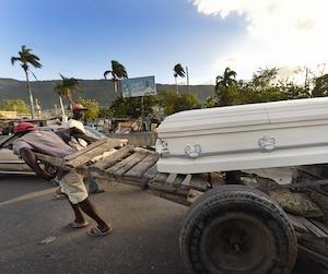 Un homme transporte à lui seul un cercueil dans les rues de Port-au-Prince.