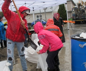 Mélanie Blais et ses deux enfants, Noémie et Alexis, sont venus aider à remplir des sac de sables pour aider les sinistrés.