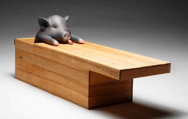 <b><i>Une histoire de petit cochon – 2016</i><br /> Bois, métal, acrylique.<br /> 11cm x 27cm x 8cm</b><br /> Pour ne pas mourir de faim alors qu'ils sont au Vietnam, les proches de Kim simulent des funérailles d'une grande tristesse pour faire passer des cochons morts dans  des cercueils.