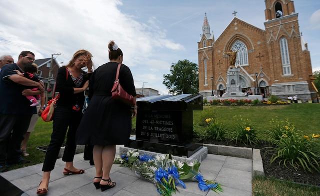 Des personnes regardent le monument en hommage aux victimes de la tragédie de Lac-Mégantic, à la suite de la messe commémorative à l'église Sainte-Agnès.