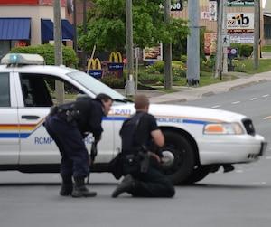 Des policiers entourant une maison où se cachait avec deux otages Justin Bourque, le tireur fou de Moncton, au Nouveau-Brunswick, le 5 juin 2014.