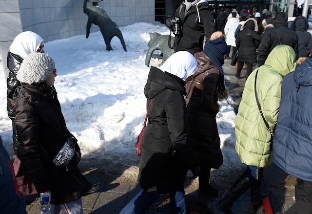 Les gens attendent avant la cérémonie funéraire au Centre des congrès de Québec en l'honneur de trois des six victimes de la tuerie de la mosquée.