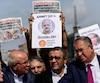 Protestors carry copies of the Cumhuriyet daily and placards of the accused during a demonstration in front of Istanbul's court house on September 25, 2017 during a hearing in the trial of journalists of the newspaper. The case, which opened in Istanbul in July, involves 17 current and former writers, cartoonists and executives from Cumhuriyet, including editor-in-chief Murat Sabuncu and chief executive Akin Atalay, and is the latest to get underway for journalists in Turkey under the state of emergency imposed after the botched putsch, fuelling growing concerns over press freedoms in the country. / AFP PHOTO / YASIN AKGUL