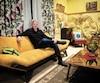 L'auteur Claude Meunier, assis au cœur du décor du salon, remonté de toutes pièces pour l'occasion.