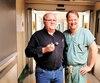 André Gauthier tenant un exemplaire de la valve qui lui a été implantée et le Dr François Dagenais, chef du Département de chirurgie cardiaque de l'IUCPQ.
