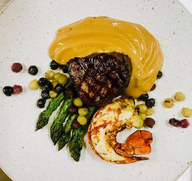Pré et marée : Filet de boeuf Galloway, queue de homard canadien à l'estragon, sauce américaine, asperges grillées et pommes de terre tricolore. Menu du chef Pierre-Laurence Valton-Simard, servis aux chefs d'État lors du G7 à La Malbaie