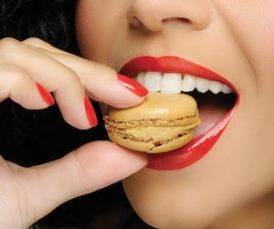 Close up to Macaroon on hand , beautiful caucasian woman eating