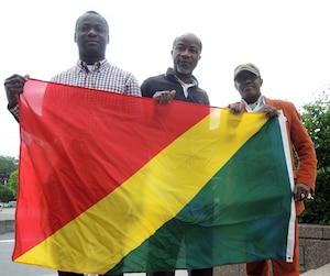 Les Congolais Socrate Bouzingou, Ludovic Mbany et Raoul Maboundou tiennent leur drapeau à l'envers pour protester contre le régime en place dans leur pays natal.