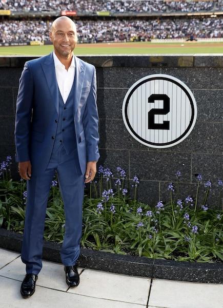 Derrek Jeter pose à côté de son numéro retiré il y a deux jours .
