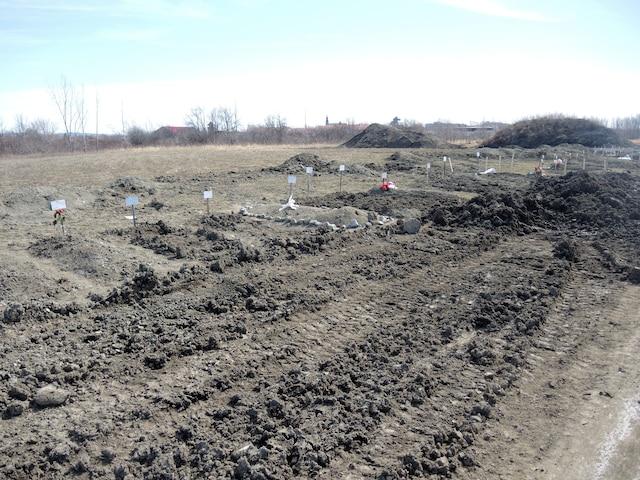 Plusieurs tombes se trouvent derrière de la terre malmenée par des travaux.