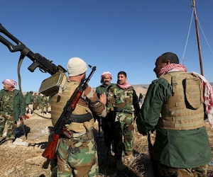 Members of the Kurdish peshmerga forces gather in the town of Sinjar