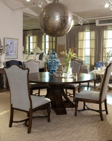 La collection Viage, montrée ici avec son lit Malacca et sa table ronde, entourée de chaises inspirées de la tradition française, offre plus d'une quarantaine d'éléments qui correspondent à l'esprit de voyage de leur nom italien. De la chambre au salon, en passant par la salle à manger.