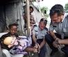 Charles-Scott Simard, policier de Québec, et Carl Viel, policier de Longueuil, inspectent le pied infecté de la petite Jemina Pharisien dans le camp Carra 2