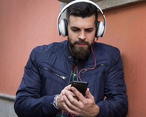 Hipster young man leaning on brown wall while listening to music with headphones. Male model holding cell phone looking for songs to select from playlist. Modern millennial generation concept