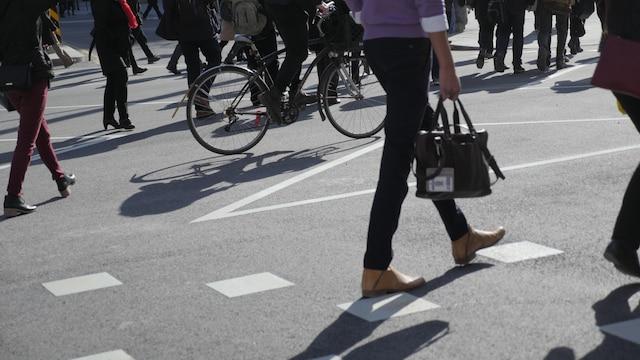 Des piétons utilisant le passage piéton à l'angle des rues McGill et Saint-Jacques