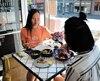 Lili Pang, de chez Mealshare, en train de déguster avec une amie un repas certifié «Mealshare» au restaurant Fieldstone à Montréal.