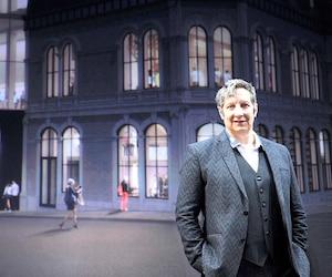 Robert Lepage pose fièrement devant une image dévoilant l'allure du théâtre le Diamant lorsque sa construction sera terminée, en 2019.