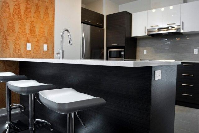 Dans l'espace ouvert des aires communes, la cuisine se démarque avec son ilot coin-repas, doté d'une pratique prise électrique sur le côté. Une petite attention qu'on appréciera à l'usage!