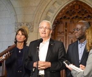 Kathleen Weil, ministre québécoise de l'Immigration, de la Diversité et de l'Inclusion, Marc Garneau, ministre fédéral des Transports, et Emmanuel Dubourg, député fédéral de Bourassa, ont fait le point sur la question des migrants irréguliers à la frontière du Québec, vendredi à Ottawa.