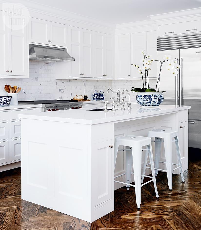 Bright white kitchen with marble backsplash.