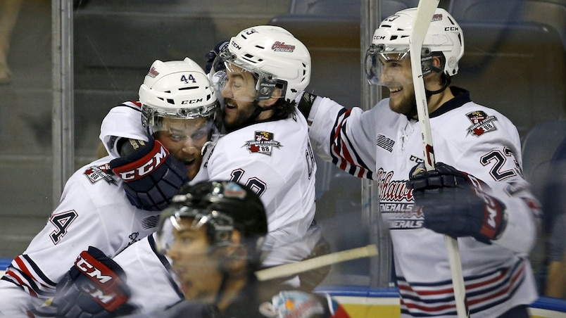 Oshawa Generals Cole Cassels celebrates with his teammates Dakota Mermis and Tobias Lindberg after he scored a goal against the Kelowna Rockets during the second period of their Memorial Cup hockey ga