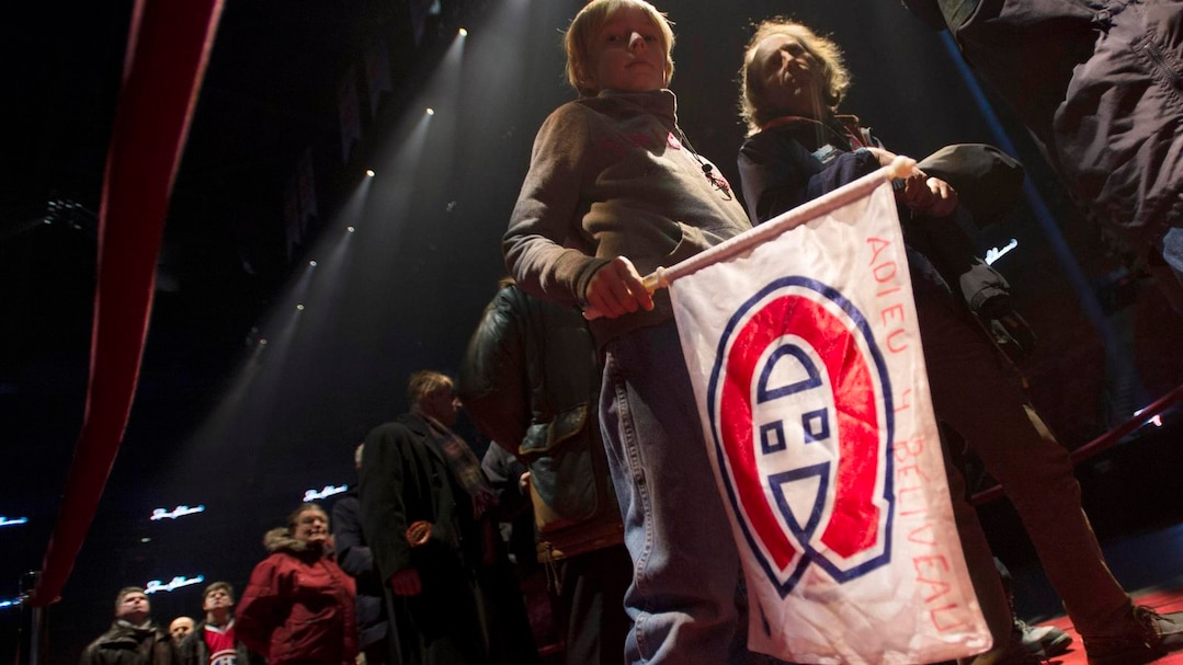 A young boy carries a team flag as mourners pay their respect to Montreal Canadiens legend Jean Beliveau during the public viewing in Montreal