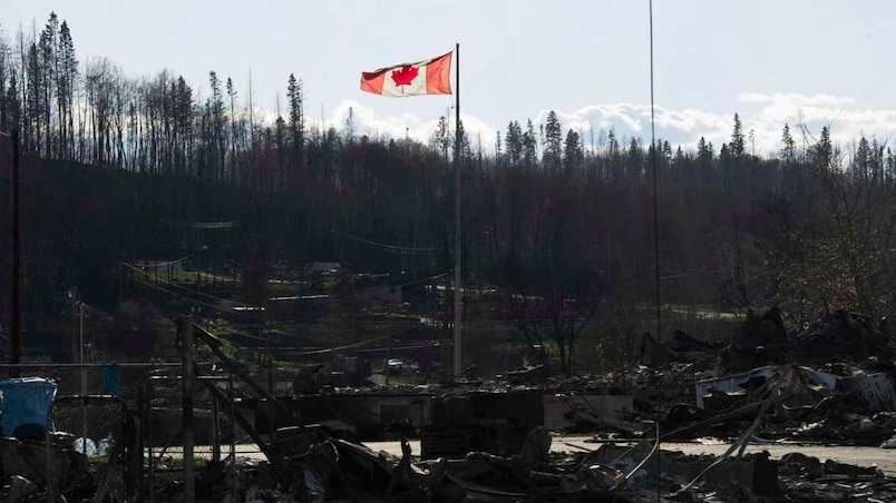 A Canadian flag flies over damage caused by a wildfire in Fort McMurray