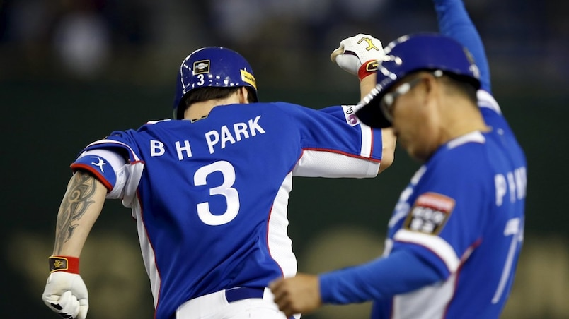 South Korea's Park reacts with coach Kim after hitting a three-run homer off Pounders of the U.S. at the Premier12 international baseball tournament at Tokyo Dome in Tokyo