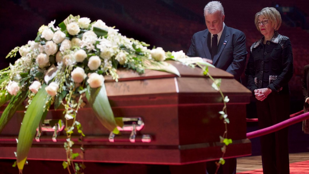 Quebec Premier Philippe Couillard and his wife Suzanne Pilote pay their respect during the public viewing for the Montreal Canadiens hockey legend Jean Beliveau in Montreal