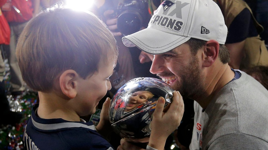 New England Patriots kicker Gostkowski shows his son Slayden the Vince Lombardi Trophy after his team defeated the Seattle Seahawks