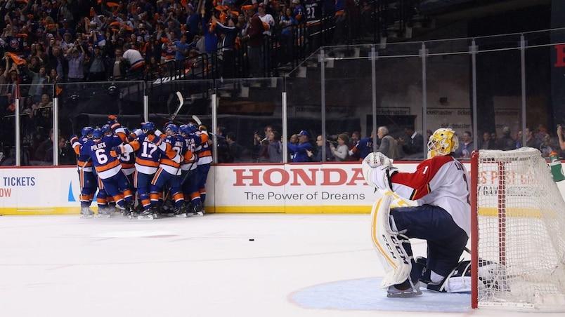 Roberto Luongo regarde les Islanders célébrer leur victoire.