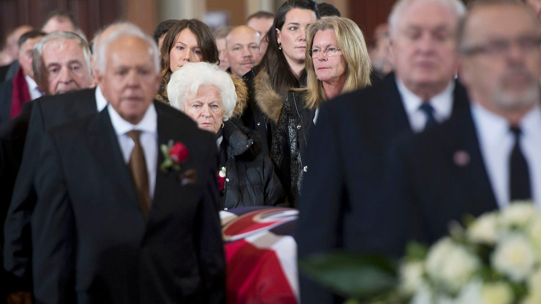 Widow Elise and daughter Helene look on as pallbearers carry the casket of former Montreal Canadiens captain Jean Beliveau in Montreal