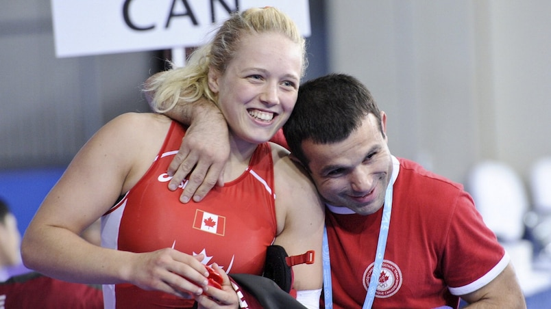 Canada's Dorothy Yeats is hugged by her coach Guivi Sissaouri after she won the gold medal in the women's 70kg wrestling after defeating South Korea's Moon Jin-