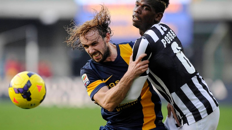 Juventus' Paul Pogba fights for an aerial ball with Hellas Verona's Marco Donadel during their Italian Serie A soccer match at Bentegodi Stadium in Verona